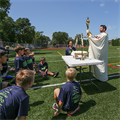 Summer camp combined football drills, scrimmages with Mass, adoration