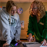 St. Joseph's Academy teacher Katie Lodes helps her students move from thinking to action