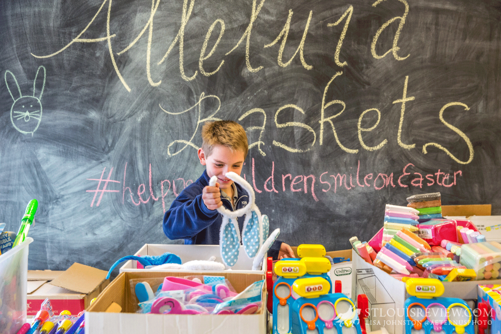 William Gnade, a second-grader at Immaculate Conception School in Old Monroe, looked for items to place into an Alleluia Basket. This year, 3,000 baskets will be given to children in need, with more than 600 volunteers helping pack the baskets.