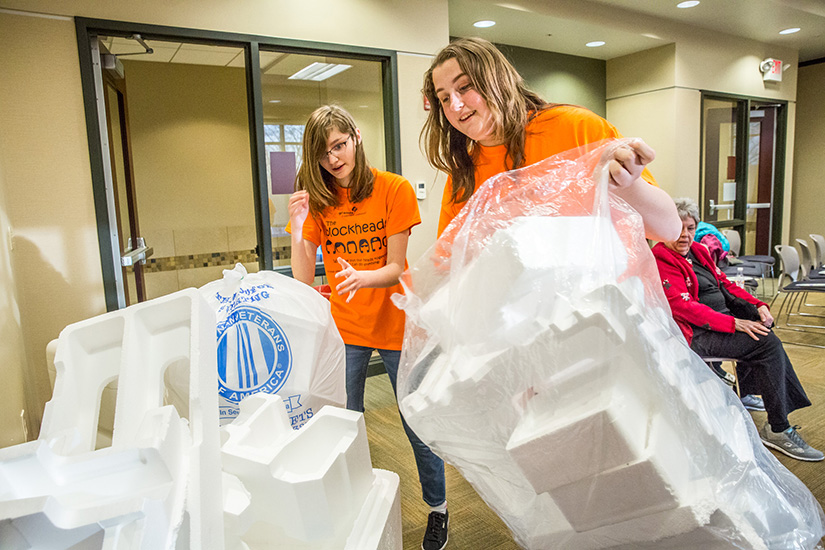 Christina Yepez, left, and Caroline Sluss stacked plastic foam, which they'll convert to an adhesive they call EcoGLOo. The girls collected foam at a recycling event at the Sunset Hills Community Center Jan. 11.