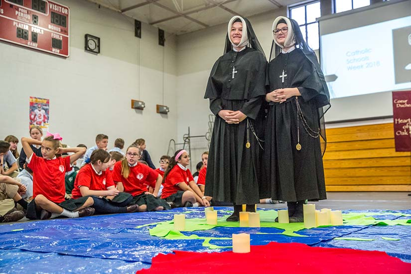To begin Catholic Schools Week, students at the Academy of the Sacred Heart gave a special presentation on the life and journey of St. Rose Philippine Duchesne. St. Rose Philippine Duchesne, portrayed by Maria Williams, and St. Madeline Sophie Barat, portrayed by Naomi Hammell, stood on a map of the world to show the voyage St. Rose Philippine Duchesne made to the United States.