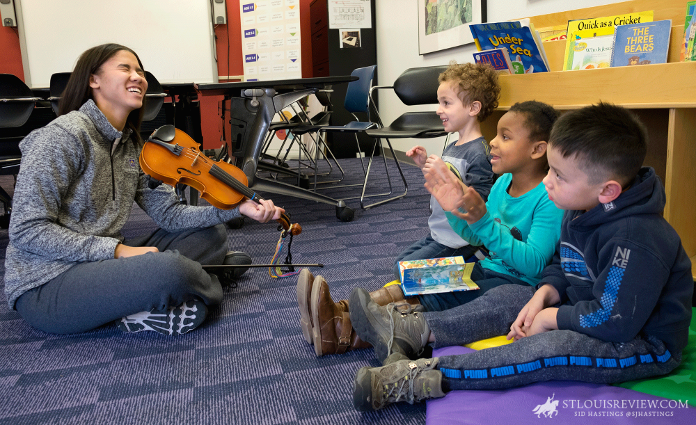 Jasmyn Mitchell demonstrated her violin skills to Maxwell Brenner, Khalie Collins and Daniel Powers, all 4, at University City Children's Center in December. Mitchell was a student at the center nine years ago and now volunteers to work with children there. She is a freshman at Rosati-Kain High School.