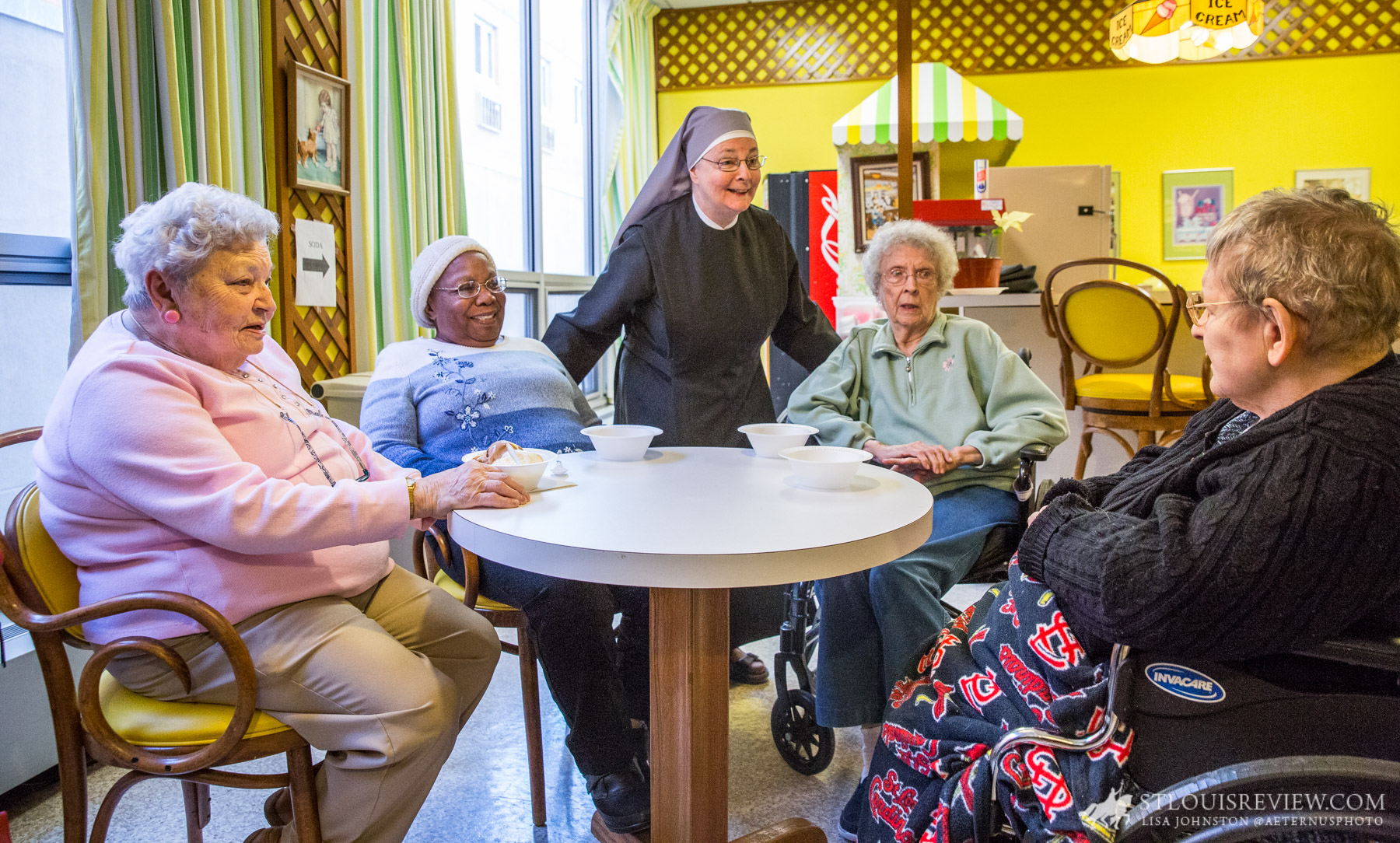 Sister Joseph Maureen Hobin, LSP, joked with residents (from left) Mary Hafner, Ester Allen, Mary Louise Doetsch and Maureen Giraffa, after they had snacks of ice cream and popcorn. The Little Sisters of the Poor continue to assist the elderly poor but support is sought for their work, including with winter heating bills.