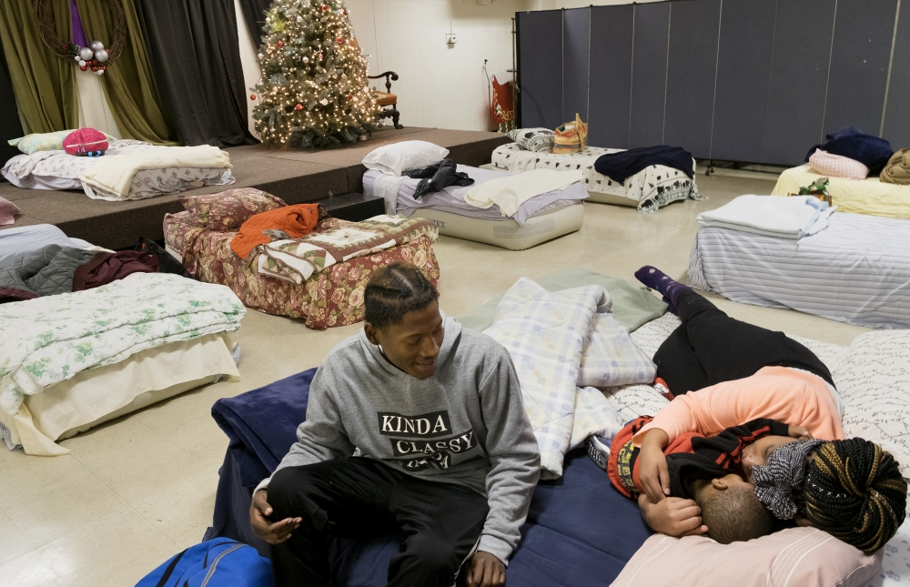 Jeremy Anderson, left, Chasidy Ellis and their one-year-old son, Chance Anderson, prepared to sleep Dec. 21 at Christ the King Church in University City. The church serves as a night site for Room at the Inn, a ministry that provides temporary emergency shelter for homeless women and families. Room at the Inn uses space in churches, synagogues and mosques to house people.
