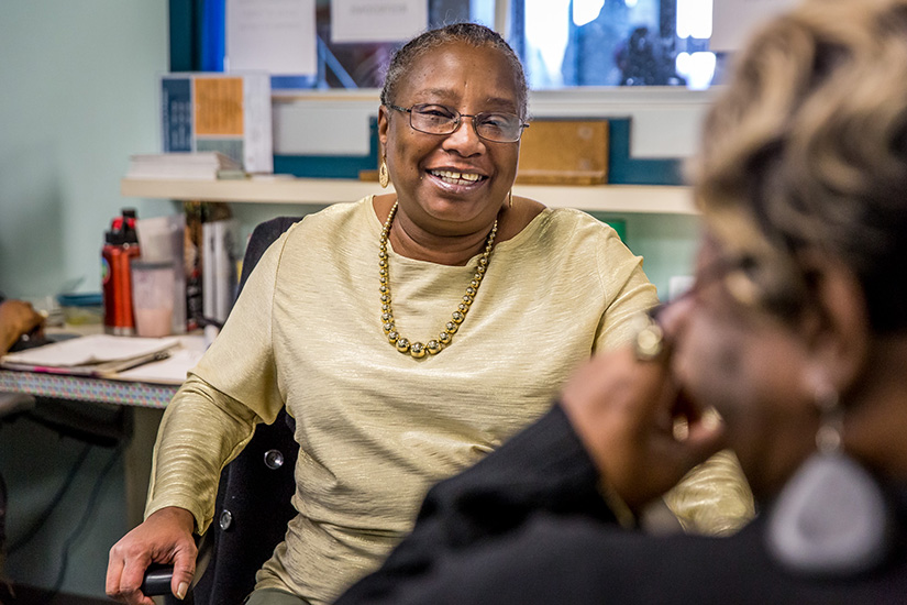 Delnita McGhaw, left, talked with housing navigator Delores Bowman Jan. 30 at her desk at St. Patrick Center. McGhaw, who was formerly homeless, works as an intake receptionist at St. Patrick Center.