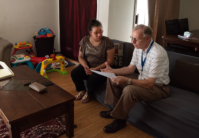Ken Kapeller, right, of the Society of St. Vincent de Paul at St. Charles Borromeo Parish, conducted a home visit June 12 with Mellissa Gaines, who has received aid through the Society.