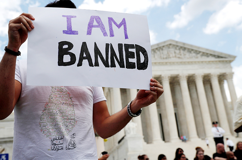 Mehrad Ansari, a university student from Iran, held a sign outside the U.S. Supreme Court building in Washington, D.C., June 26. After the Supreme Court upheld the travel ban on several predominantly Muslim countries including Iran, Ansari said he cannot go home to see his family now if he wants to return to the U.S.