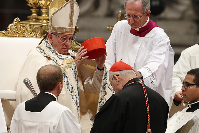 Pope Francis placed a red hat on new Cardinal Louis Raphael I Sako, the Chaldean Catholic patriarch, at a consistory at which the pope created 14 new cardinals June 28 in St. Peter's Basilica.