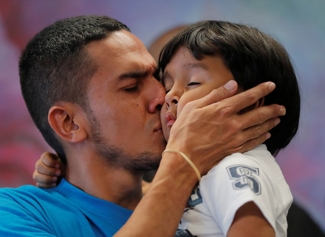 Javier, a 30-year-old immigrant from Honduras, kissed his 4-year-old son, William, July 11 in New York when they were reunited after being separated for 55 days during detention at the Texas border. Catholic Bishops' Migration and Refugee Services and Catholic Charities USA are among the organizations helping reunite children separated from family at the border.