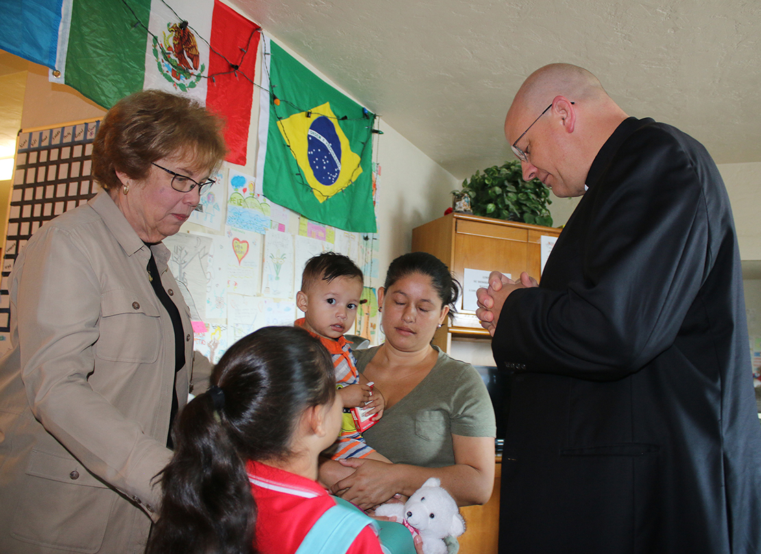 Dominican Sister Donna Markham, president and CEO of Catholic Charities USA, and Bishop Edward J. Weisenburger of Tucson, Ariz., prayed July 12 with a young family moments before they leave Casa Alitas, a family shelter in Tucson, for a bus trip that will take them to family in Baltimore.
