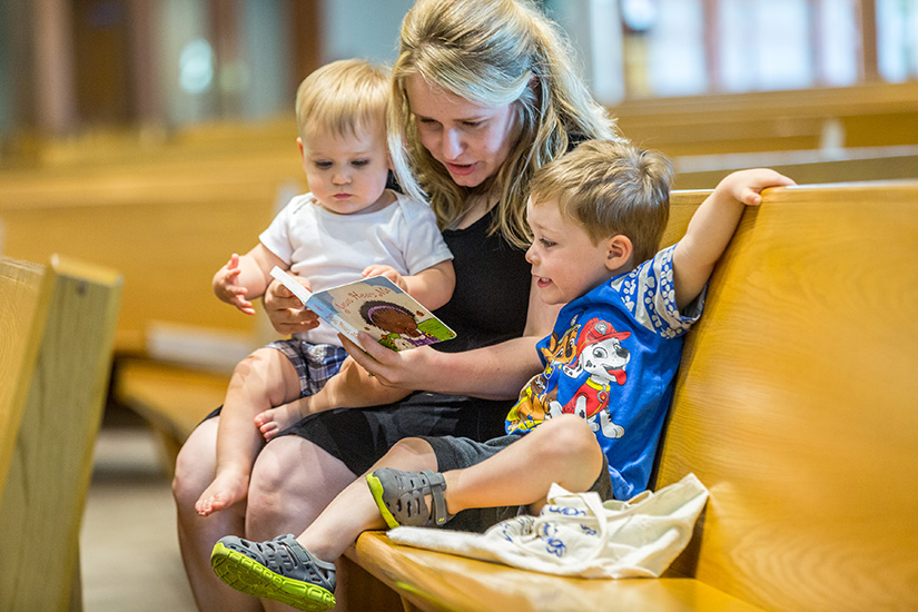 Melissa Bommarito read a book to her sons, 18-month-old Lucas and 3-year-old Henry, before Mass at St. Catherine Laboure Parish.
