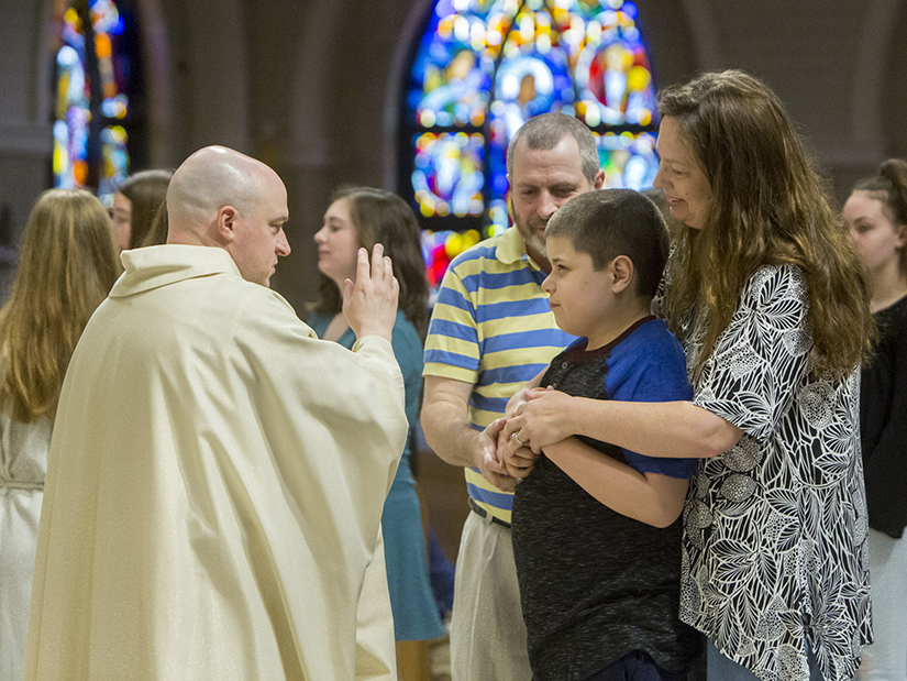 Father James Theby blessed Eli Homyk at the All Abilities Mass at Our Lady of Lourdes Church in Washington. Eli attended the Mass with his parents, Chris, center, and Stacey, right, and his sister Elizabeth.