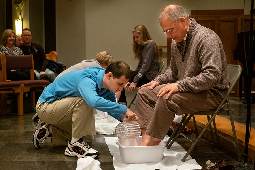 John Houston washed the feet of his father, Steve Houston, at Holy Thursday Mass at Sacred Heart Church in Valley Park. John has autism, and the family has helped the parish become a more welcoming place for children with disabilities.