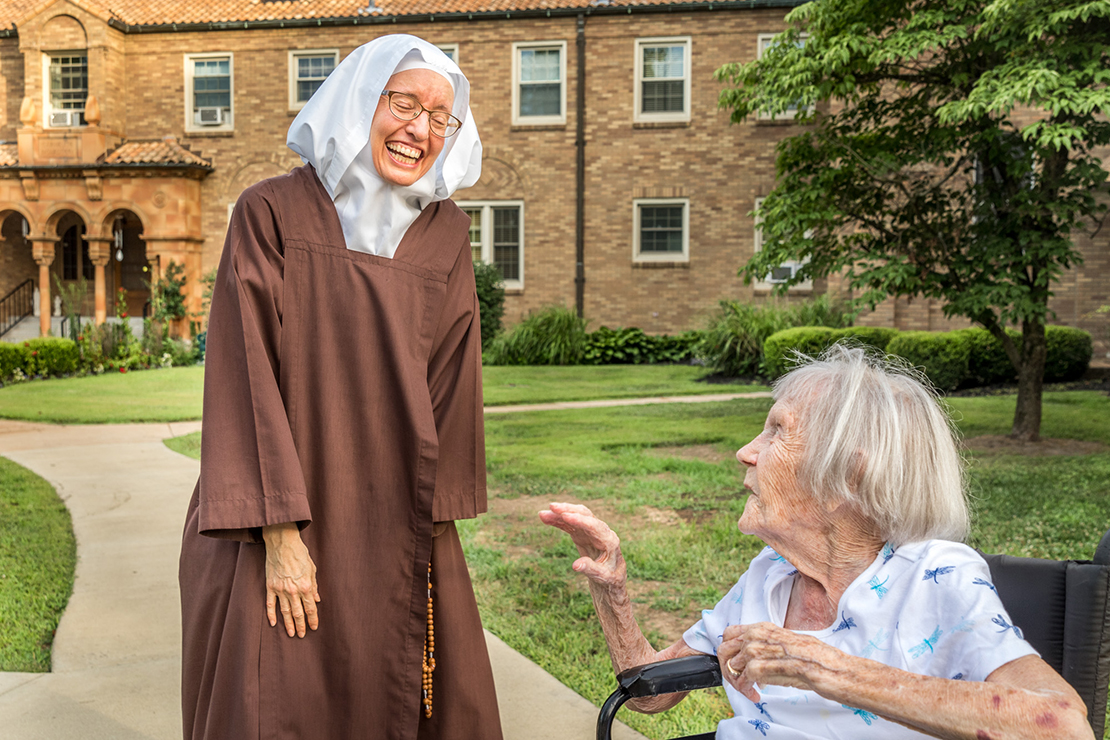 Sister Helen Marie of the Holy Eucharist talked with 94-year-old Catherine Rozycke before the start of the Novena to Our Lady of Mount Carmel on July 19. Rozycke, a parishioner at Queen of Peace in Belleville, Ill., has attended the annual outdoor novena for the entire 70 years it has existed.