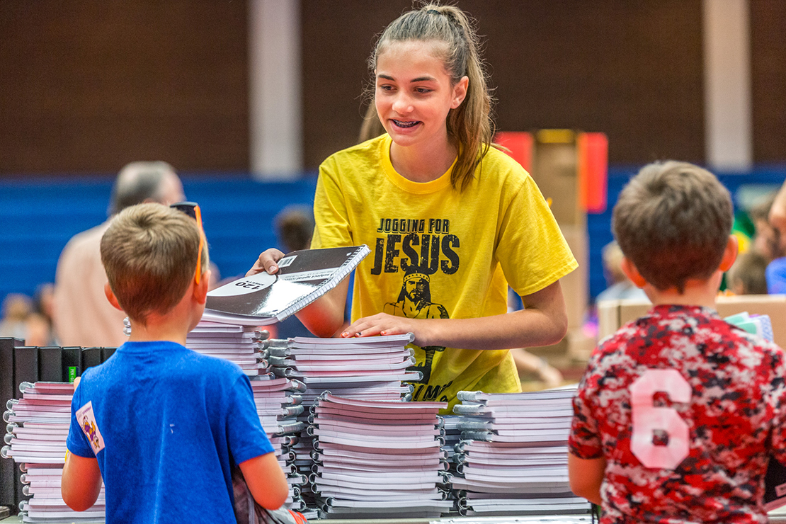 Shea Block, a member of the St. Vincent de Paul youth group at Our Lady Queen of Peace Parish in House Springs, smiled as she distributed notebooks for students of low-income families.
