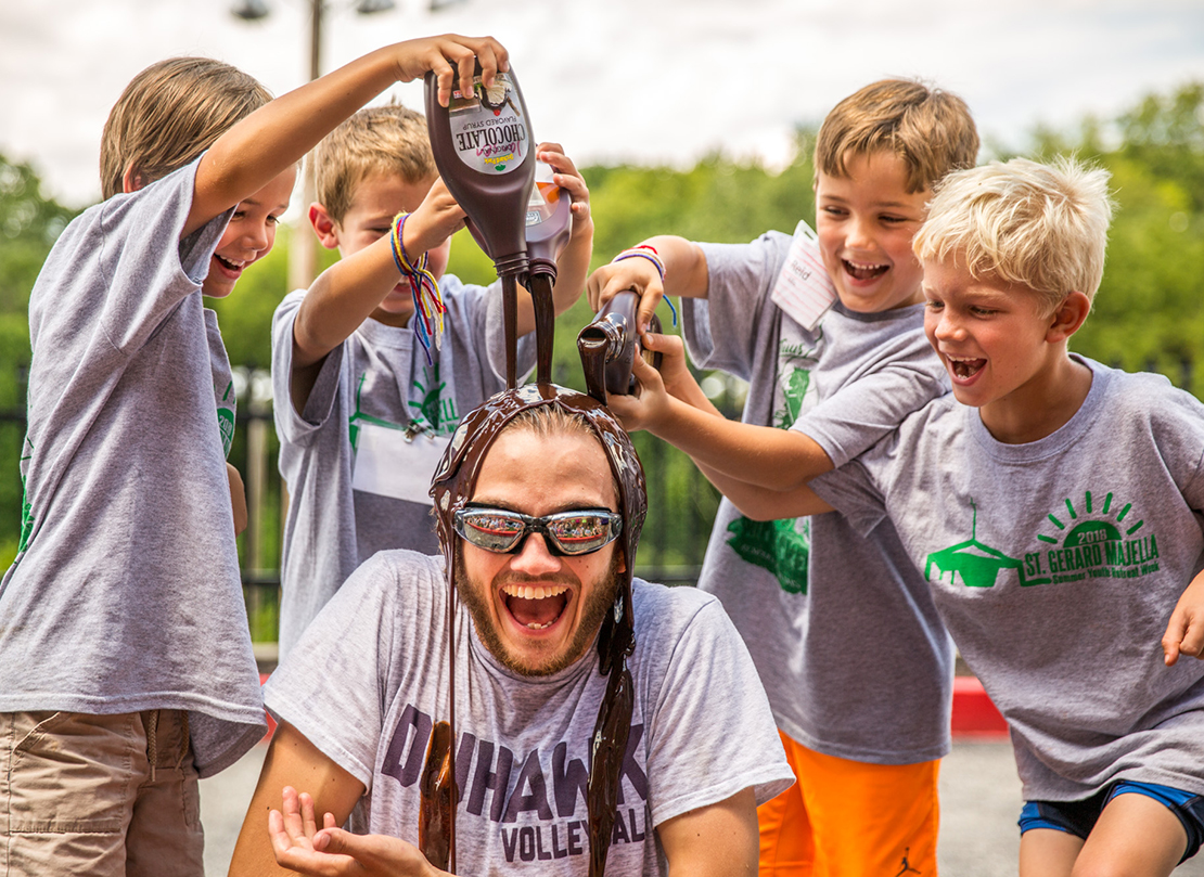 Sam Gerbic, a Totus Tuus misionary from Incarnate Word Parish, was transformed into a human sundae on July 27 as, from left, Giorgio Jansen, Jacob Wolf, Reid Ellis and Tommy Schneller poured chocolate sauce on him.