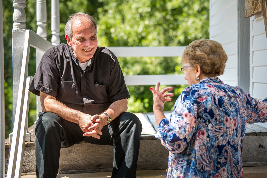 Father Rickey Valleroy talked with Veneita Carron on the steps of a one-room schoolhouse museum next to St. Lawrence Church in Lawrenceton. Father Valleroy recently became the pastor of St. Lawrence in Lawrenceton and St. Agnes in Bloomsdale after recovering from health issues.