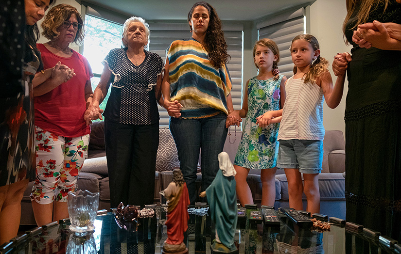 Catholics of Brazilian heritage, including Suzy McBride, left, Jaqueline Shafer, Vera Lemos, Ana Carolina McGinn, Maya McGinn, 10, Olivia Carr, 7, and Rogeria Lemos, joined hands in prayer at a Grupo da Misericrdia (Divine Mercy) prayer group meeting Aug. 17.