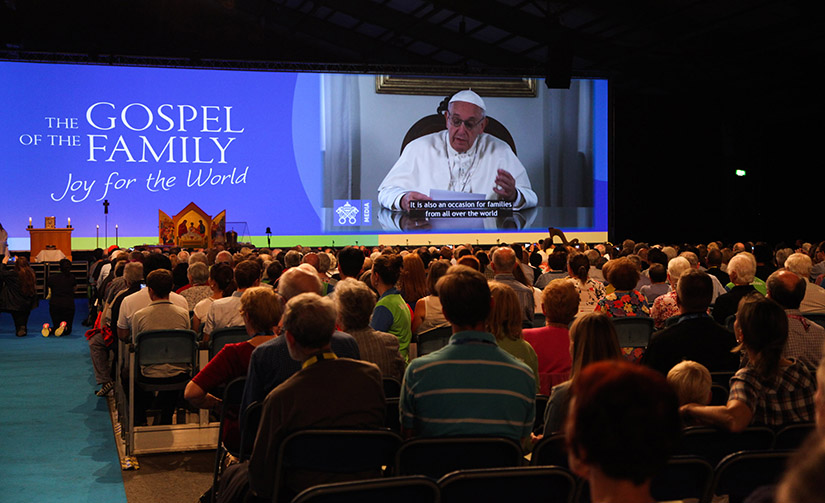 Attendees watched Pope Francis on a screen during the opening ceremony of the World Meeting of Families in Dublin Aug. 21. The pope will visit Ireland Aug. 25-26.