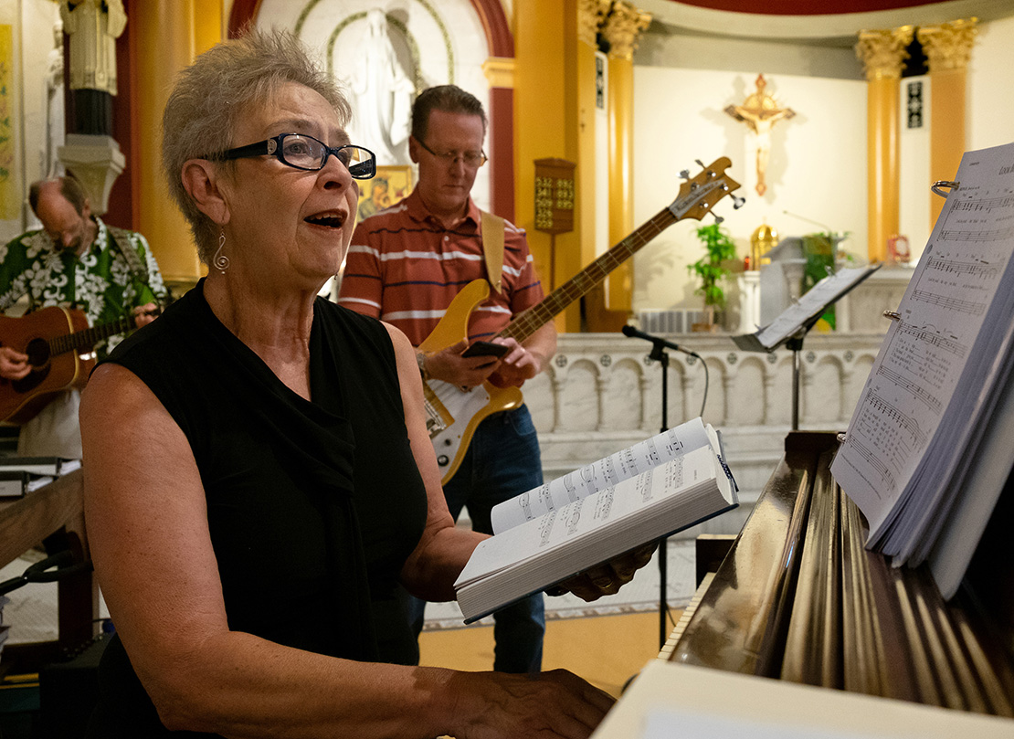 "Ruth Ehresman, director of the St. Pius V Church choir, played the piano as the choir members practiced before Mass at the church. ""We have a wonderful group of folks in the choir who enjoy singing, are committed and enjoy leading the singing,"" Ehresman said."