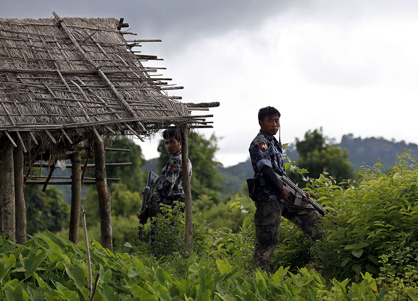 Police stand guard in 2017 after finding 10 bodies buried in a mass grave in the village of Maungdaw, Myanmar. A U.N. fact-finding mission said senior military officials in Myanmar must be prosecuted for genocide and war crimes against Rohingya Muslims and other ethnic minorities.