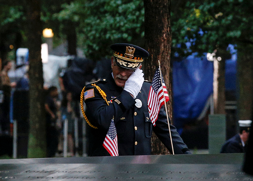An officer mourned at the National September 11 Memorial and Museum during ceremonies Sept. 11 marking the 17th anniversary of the attacks in New York. Nearly 3,000 people died in the attacks in New York City, Shanksville, Pa., and at the Pentagon.