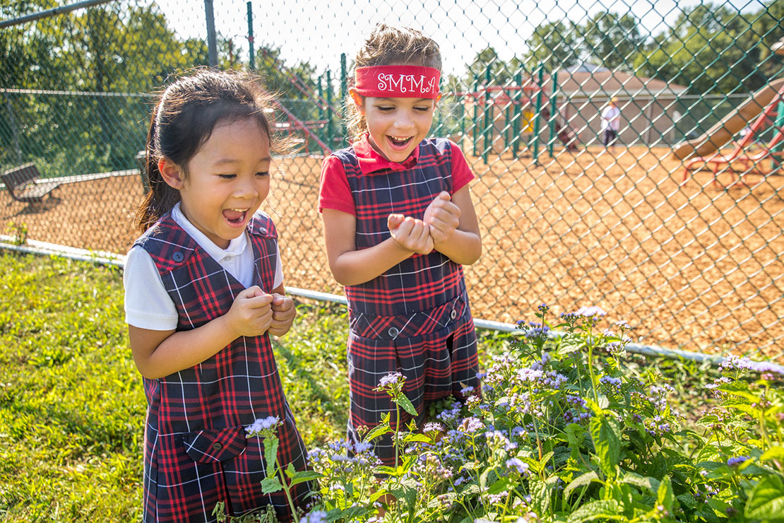 Kindergarten students Jacquelin Vu and Juliana Talleur reacted to seeing moths flying through flowering mint in a butterfly garden at St. Margaret Mary Alacoque School Sept. 18.