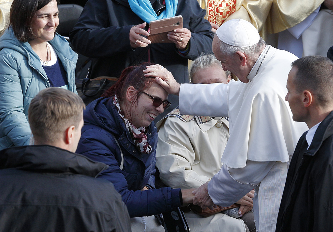 Pope Francis greets a woman as he meets the disabled before celebrating Mass in Freedom Square in Tallinn, Estonia, Sept. 25.