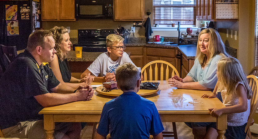 Melinda Kruper, right, of Assumption Parish in O'Fallon, visited with Jason and Misty Koenic and their children, Sam, Ethan and Maria, at their home on Aug. 1.