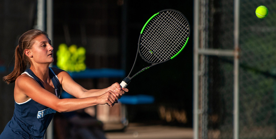 "Emilie Meyer, a tennis player at St. Dominic High School, returned a shot against Nerinx Hall High School. Emilie, a freshman, said she enjoys playing with her sister, Kaylie. ""It's always fun to have her by my side,"" Emilie said."