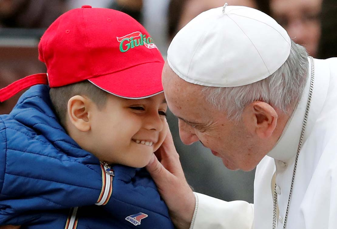 Pope Francis greeted a child as he arrived to lead his general audience Oct. 31 in St. Peter's Square at the Vatican.