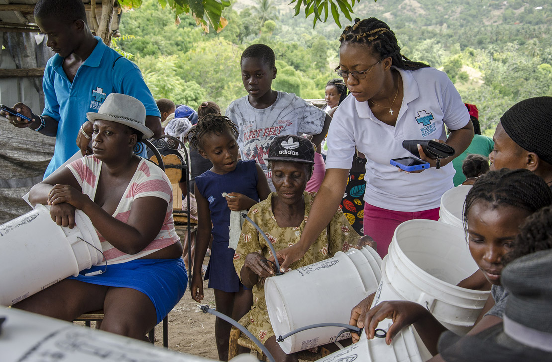 "A Water With Blessings teacher in Anse-a-Veau, Haiti, collected GIS data and checked on hardware installation at the end of a training. Water With Blessings trains ""water women"" in impoverished countries to properly use filtration systems and maintain a clean water supply."