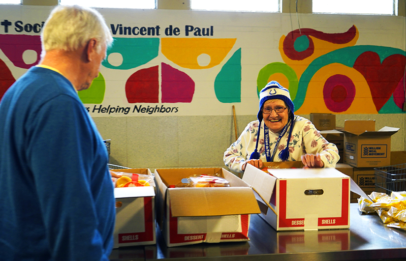 Volunteer Dee Poteet opened a new box of dessert shells to distribute to clients Nov. 15 at the Catholic-run Indianapolis food pantry operated by the Indianapolis Council of the Society of St. Vincent de Paul.