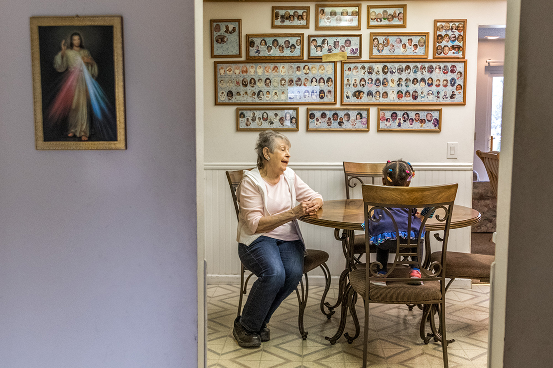 Marie Peters talked with her foster child, Noel, in the kitchen on Nov. 12. Marie and her husband Ron have been adopting and fostering children since the 1960s. The pictures along the back wall of their kitchen feature many of the almost 200 children they have fostered.