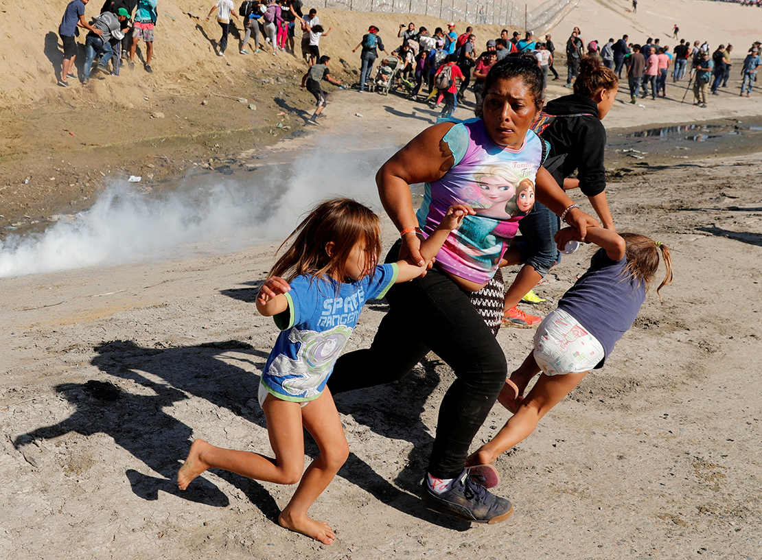 A Honduran migrant family, part of a caravan trying to reach the United States, ran from tear gas released by U.S. border patrol Nov. 25 near the border fence in Tijuana, Mexico.