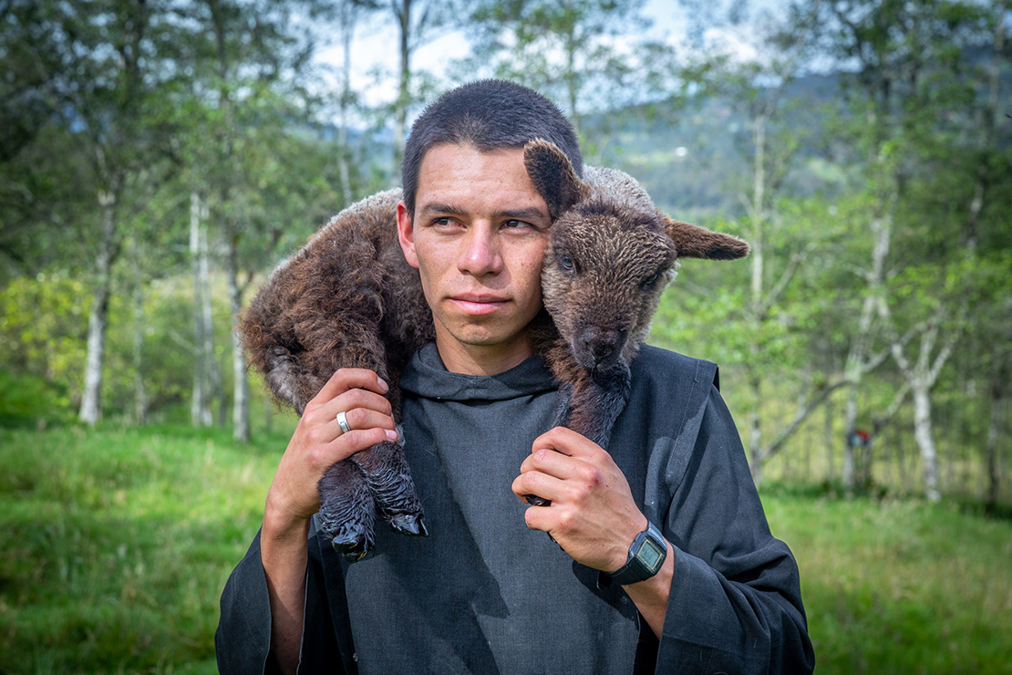 Brother Jeffers de Nuestra Señora de Guadalupe carried a sick lamb as he moved sheep to a different pasture at the monastery of Our Lady of Guadalupe in Arcabuco, Colombia.