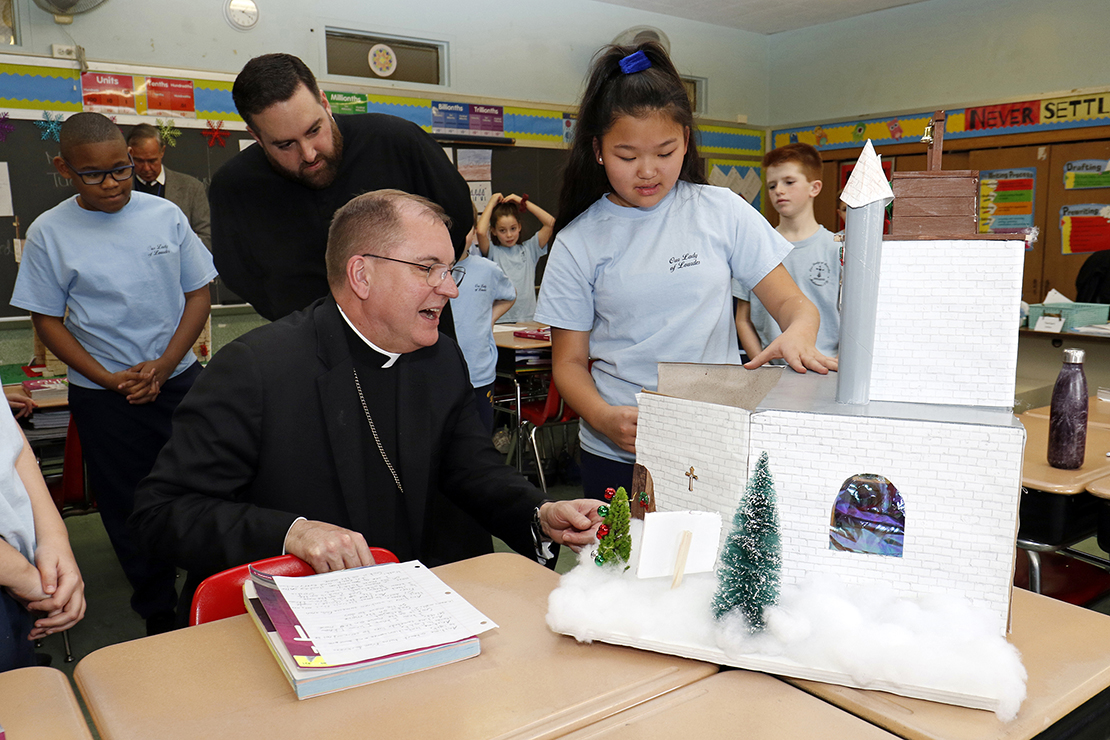 Bishop John O. Barres of Rockville Centre, N.Y., looked at a model of a church building designed and constructed by fifth-grader Emma McDermott at Our Lady of Lourdes School in Malverne, N.Y., Jan. 28. Bishop Barres is visiting schools throughout his diocese as they celebrate Catholic Schools Week, observed Jan. 27 through Feb. 2 this year.