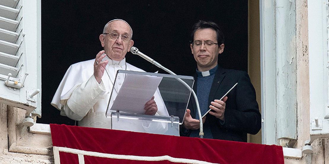 "Pope Francis stood neext to Jesuit Father Frederic Fornos, head of the Pope's Worldwide Prayer Network, during the Angelus led from the window of his apartment overlooking St. Peter's Square at the Vatican Jan. 20. The pope used a tablet held by Father Fornos to launch ""Click to Pray,"" a new mobile app and online platform."