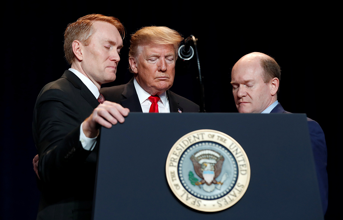 U.S. President Donald Trump prayed with Sens. James Lankford, R-Okla., and Chris Coons, D-Del., at the National Prayer Breakfast in Washington Feb. 7.