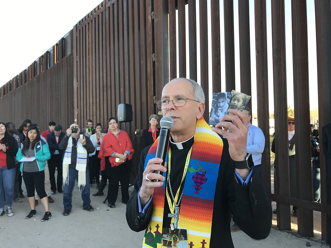 Bishop Mark J. Seitz of El Paso, Texas, held photos of two migrant children who died in U.S. custody; he spoke during the Feb. 26 Interfaith Service for Justice and Mercy at the Border near Sunland Park, N.M.