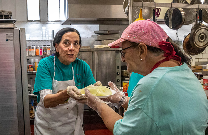 Nicky Hoxworth, left, handed a plate of onions to fellow volunteer Schareen Fichtenmeyer at the Most Holy Trinity Parish fish fry. Hoxworth and Vickie Deason spearheaded the return of fish fries at the church after about a 20-year hiatus.