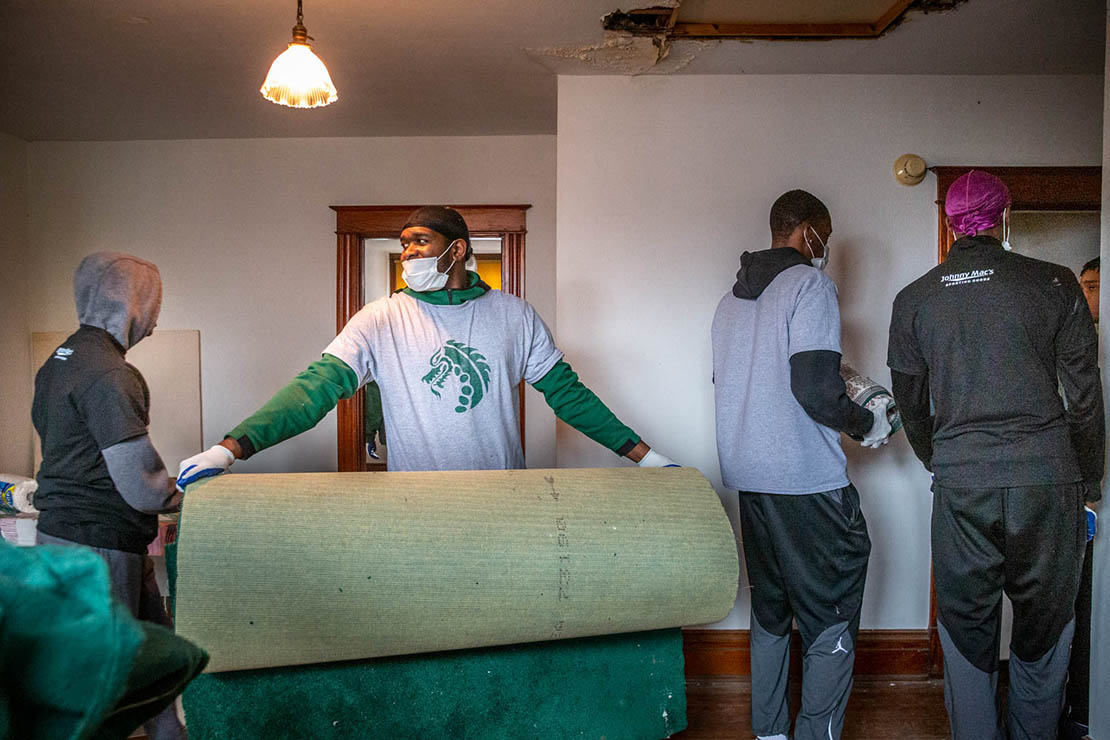 The St. Joseph Housing Initiative began work on a south St. Louis home on March 2. Damond Wiley carried a piece of carpet as the basketball team from St. Mary's High School volunteered to clean out the house the day after they won the district basketball championship.