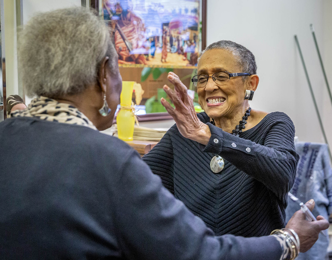 Gloria Taylor, co-founder of Community Women Against Hardship, spoke with longtime friend and social worker Bernice Thompson at the organization's Family Support Center in the Vandeventer neighborhood of St. Louis. Community Women Against Hardship was honored with the Torchbearer Award by the St. Charles Lwanga Center.