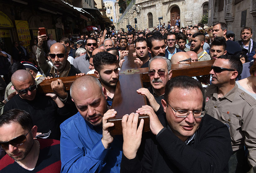 Mousa Kamar, front right, and his son, Youssef, far left corner, carried the large wooden cross during the Good Friday procession on the Via Dolorosa in Jerusalem's Old City March 25, 2016. Mousa Kamar and his sons are carrying on the tradition of his grandfather and father in carrying the cross on Good Friday.