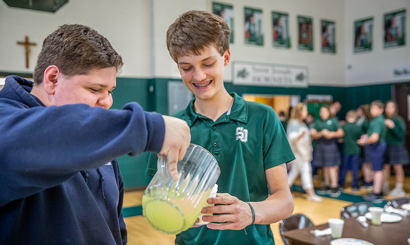 St. Joseph School in Farmington eighth-grader Brayden Armes, center, won the Southeast Missouri Regional Spelling Bee and will compete in the Scripps National Spelling Bee in Maryland. He helped classmate T.J. Benoist set tables for lunch at St. Joseph School.