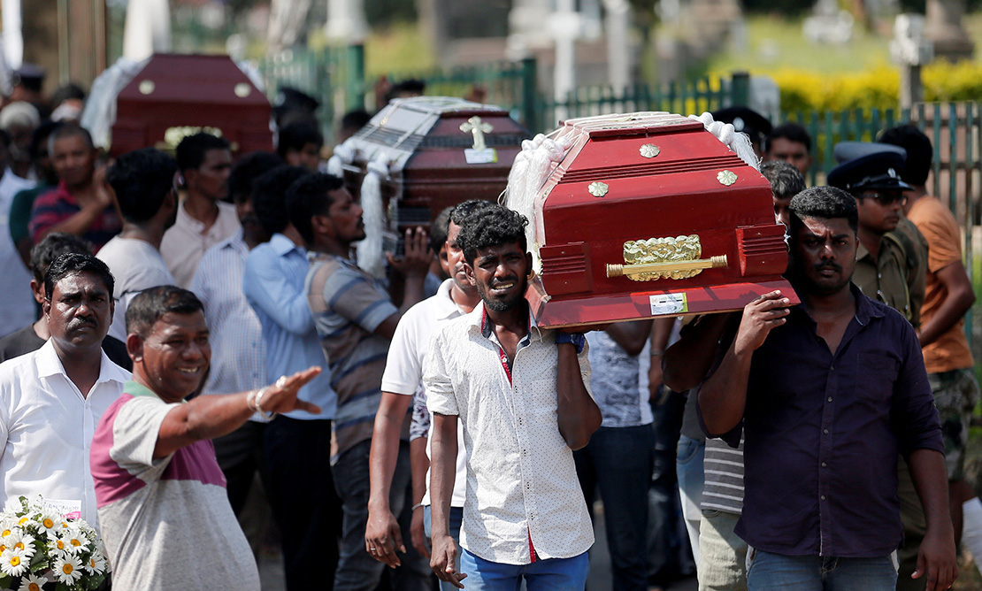 People carried the caskets of victims during a mass burial for victims of bomb attacks in Colombo, Sri Lanka, April 23. More than 250 people were killed in a string of suicide bomb attacks on churches and luxury hotels across the island April 21.