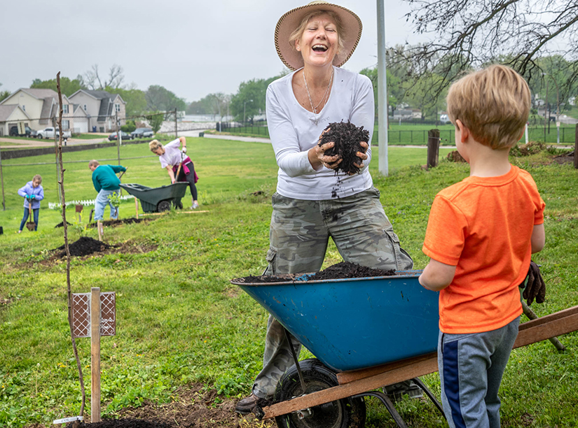 "Angie Freshley, a parishioner at Our Lady of the Holy Cross in Baden, laughed at her 3-year-old grandson, Henry Dugan, as they mulched a newly planted tree in the parish's orchard. Freshley helped spearhead the planting of the orchard as one way to respond to Pope Francis' call to care for the environment in his encyclical, ""Laudato Si'."""