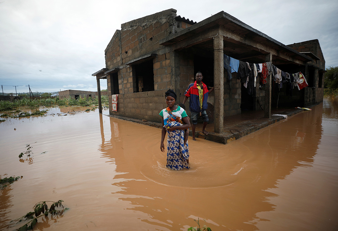 Agiro Cavanda and his wife, Agera, waded through floodwaters outside their home in Pemba, Mozambique, April 29, in the aftermath of Cyclone Kenneth. Aid workers are struggling to find families to reunite with children who lost parents when a pair of cyclones hit the country.