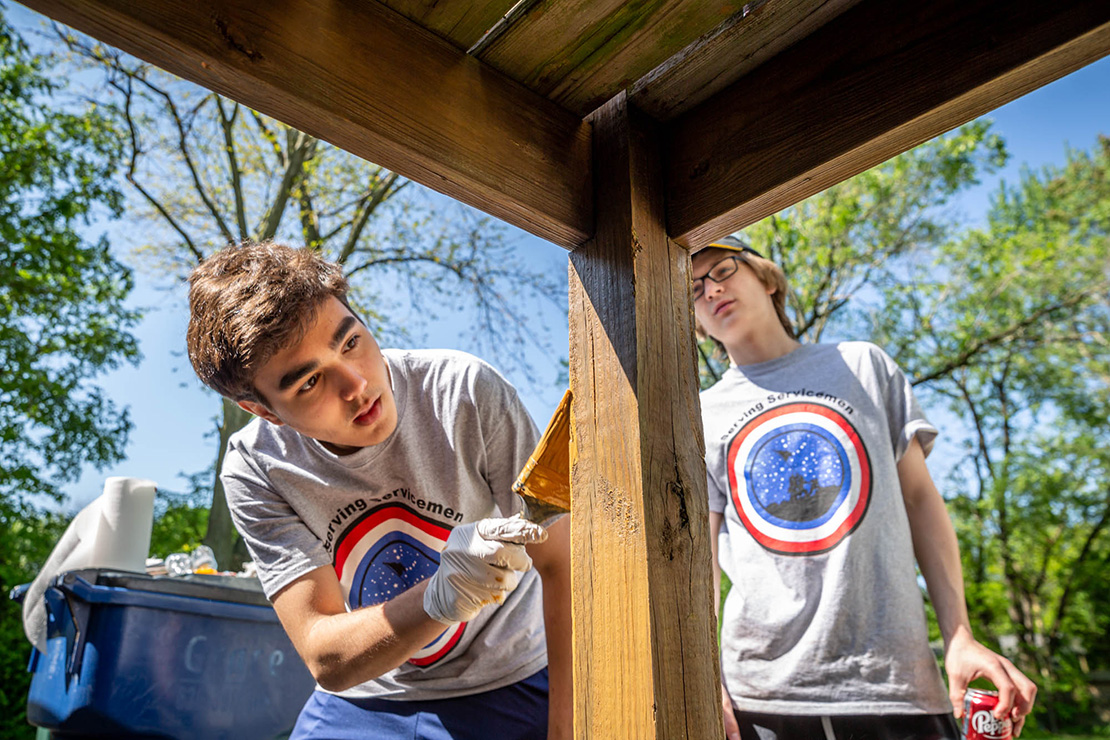 Jack Hood and Alex Flerlage stained a deck at the home of Dale and Carol Wiseman in St. Peters on May 14. The Christian Brothers College High School students are part of Serving Servicemen service organization that assists veterans.