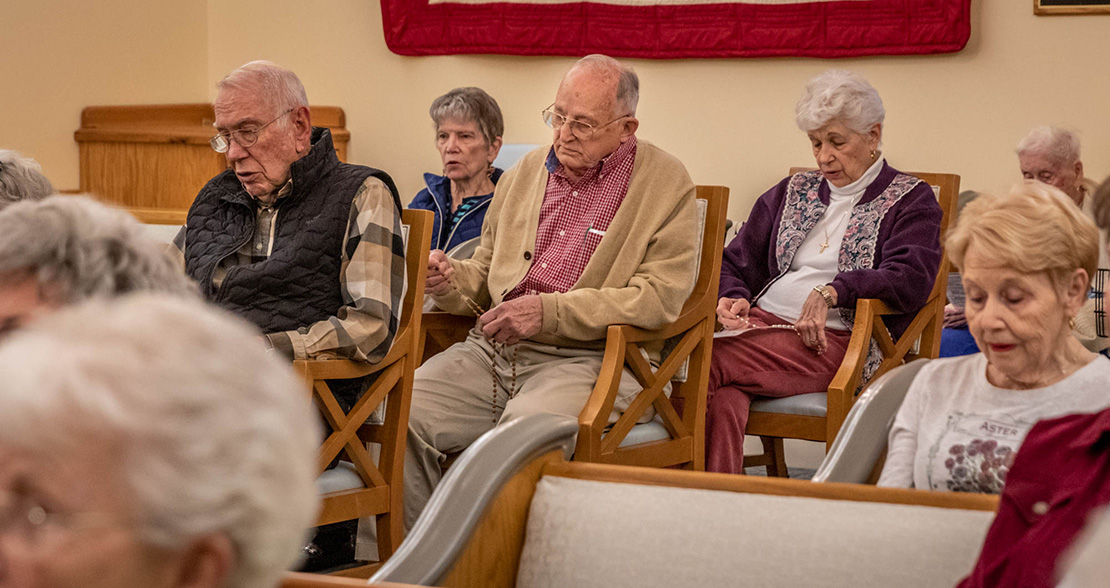 Charles Scherrer, center, 83, led the Rosary at Friendship Village in Sunset Hills April 1. Scherrer, who has been a parishioner of St. Elizabeth of Hungary since 1961, has been instrumental in the formation of a tight-knit Catholic community at the facility.